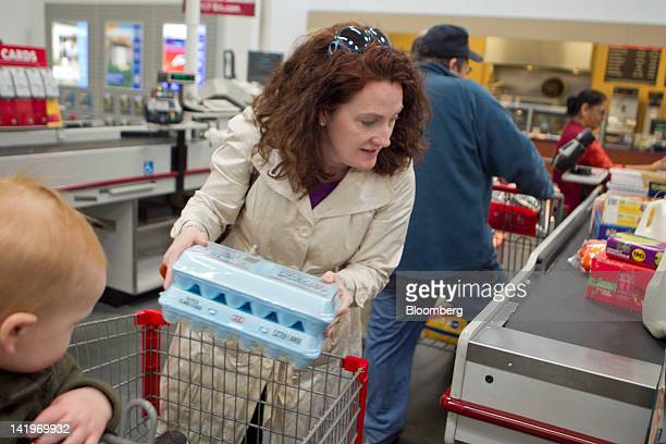 Customer Kelly Murray puts items on the conveyor belt at a cash register in a BJ's Wholesale Club Inc store in Falls Church Virginia US on Tuesday...