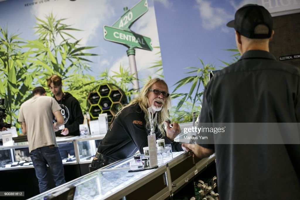 Customer Kurt Elvis, center, talks to 420 Central employee Kevin Gardner, right, on the first day of legal recreational pot sales at 420 Central, in Santa Ana, Calif., on Jan. 1, 2018. The state has issued dozens of permits for retailers to begin recreational sales this week, expanding a market that is expected to grow to $7 billion annually by 2020. Several of those retailers are in West Hollywood, but they won't open until Tuesday at the city's request. That makes Santa Ana's licensed stores the closest option for Angelenos who want to buy recreational marijuana on New Year's Day. Buyers could also trek to San Diego or the Palm Springs area to purchase pot.