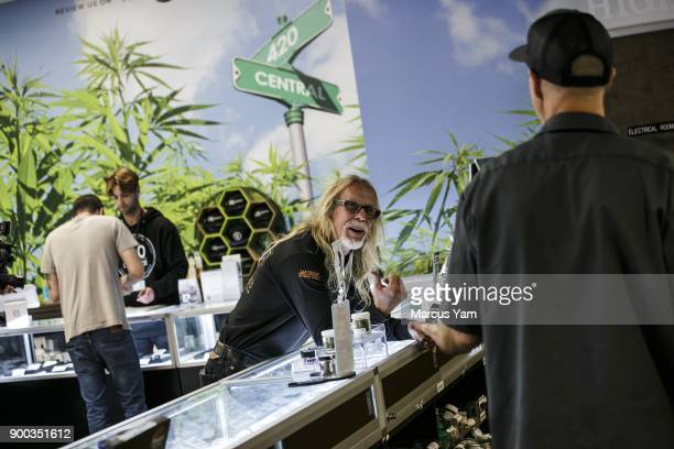 Customer Kurt Elvis center talks to 420 Central employee Kevin Gardner right on the first day of legal recreational pot sales at 420 Central in Santa...