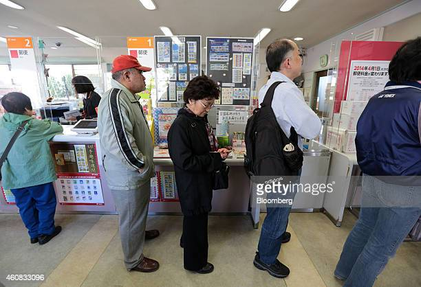 Customer Kyoko Yamamoto center waits in line to use an automated teller machine at a Japan Post Co branch in Hachioji Japan on Tuesday April 15 2014...
