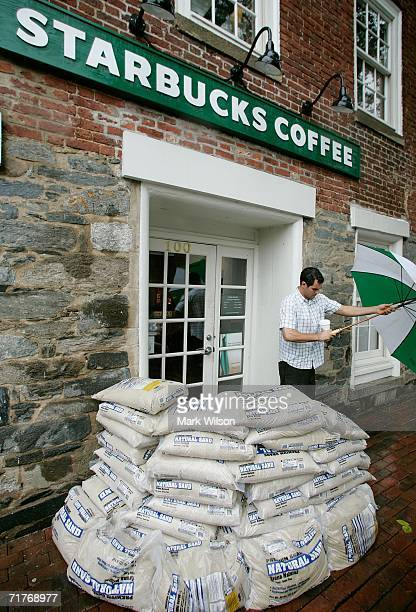 A customer leaves a Starbucks where sandbags are stacked at the front door September 1 2006 in Alexandria Virginia Tropical Storm Ernesto is passing...