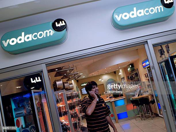 A customer leaves a Vodacom shop in Cape Town South Africa Thursday November 3 2005 Vodafone Group Plc the world's biggest mobilephone company plans...