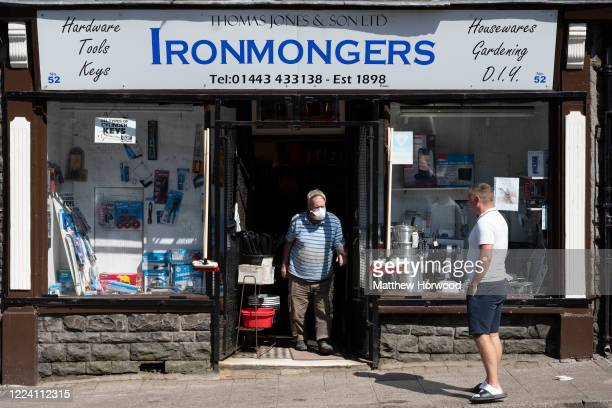 Customer leaves an Ironmongers store wearing a surgical face mask as another customer waits outside on May 06, 2020 in Penygraig, United Kingdom. The...