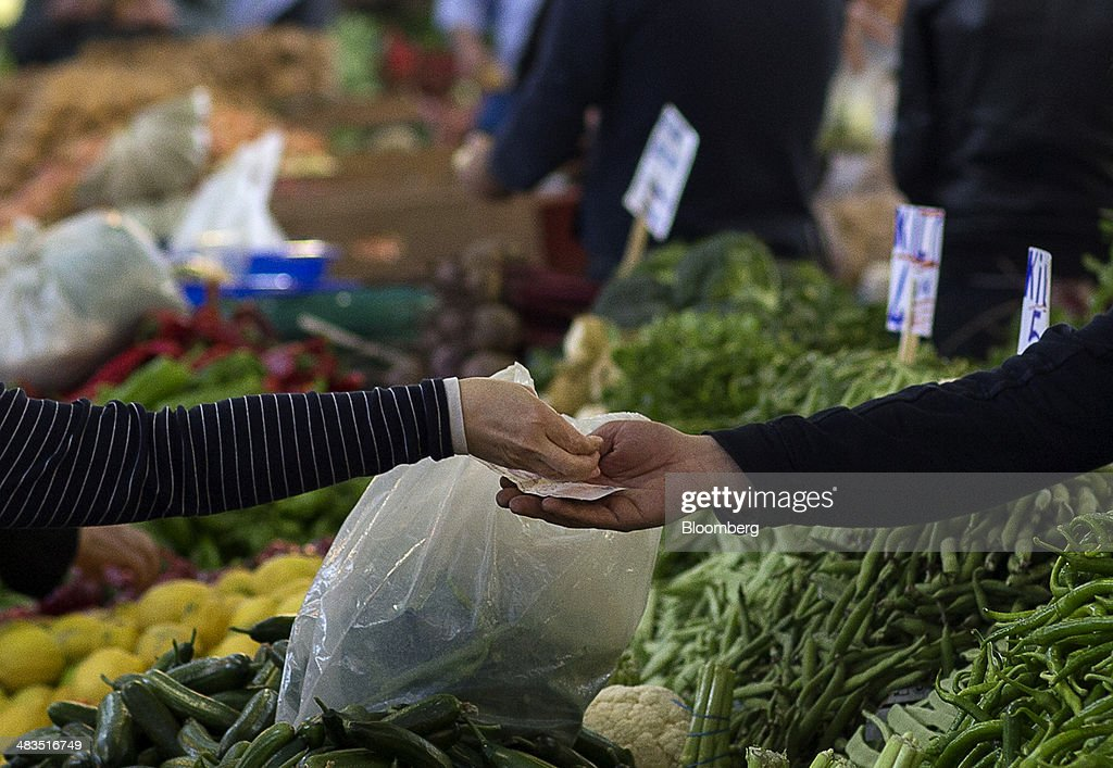 A customer, left, hands over lira banknotes and coins in payment for vegetables purchased at a stall in the Yesilkoy street market in Istanbul, Turkey, on Wednesday, April 9, 2014. Turkish central bank Governor Erdem Basci indicated to analysts in London on April 3 that he planned to keep monetary policy tight to control inflation. Photographer: Kerim Okten/Bloomberg via Getty Images