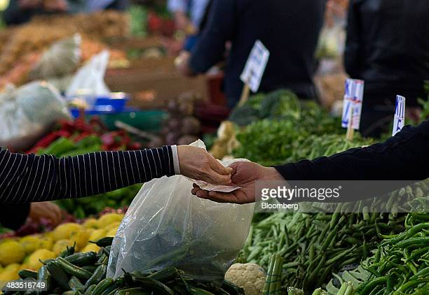 A customer left hands over lira banknotes and coins in payment for vegetables purchased at a stall in the Yesilkoy street market in Istanbul Turkey...