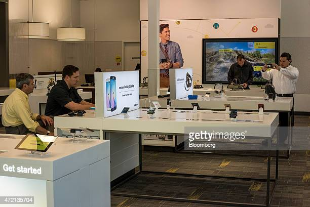 Customer, left, is helped by an employee inside a Sprint Corp. Store in Palo Alto, California, U.S., on Friday, May 1, 2015. Sprint Corp. Is...