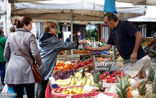 A customer left pays for her purchase from a fruit and vegetable stall at Campo dei Fiori outdoor street market in Rome Italy on Monday March 3 2014...