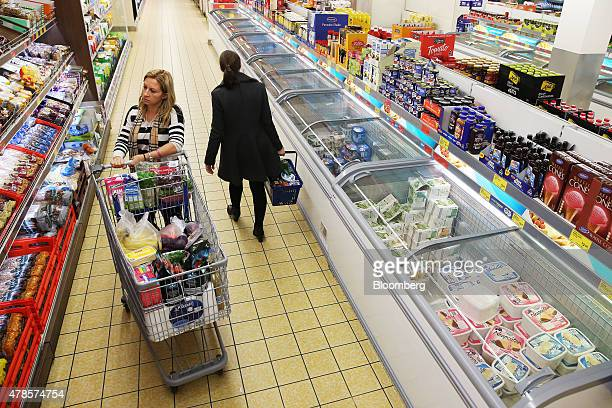 A customer left pushing a shopping cart browses a display of bread at an Aldi Stores Ltd food store in Sydney Australia on Thursday June 25 2015...