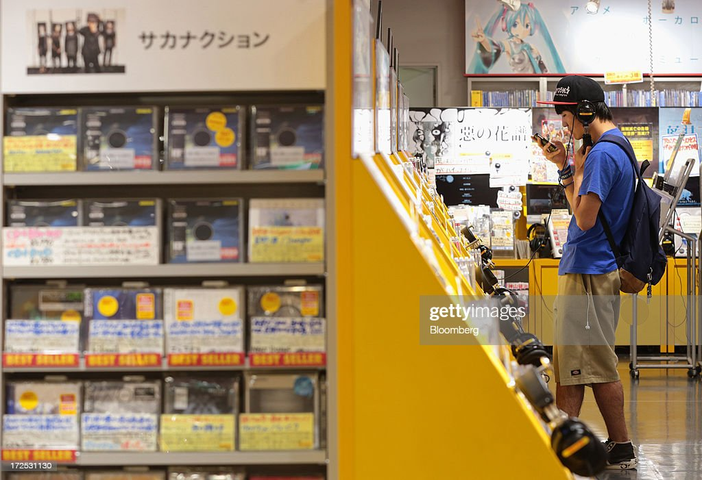 A customer listens to music while using a mobile device at a Tower Records Japan Inc. store in Tokyo, Japan, on Monday, July 1, 2013. Music sales in the country rose for the first time in five years, led by tunes delivered on CDs and other physical media, bucking the trend in developed markets as cheaper downloads gain ground. Physical media made up 82 percent of Japanese music sales last year, versus 37 percent in the U.S., said the Recording Industry Association of Japan. Photographer: Yuriko Nakao/Bloomberg via Getty Images