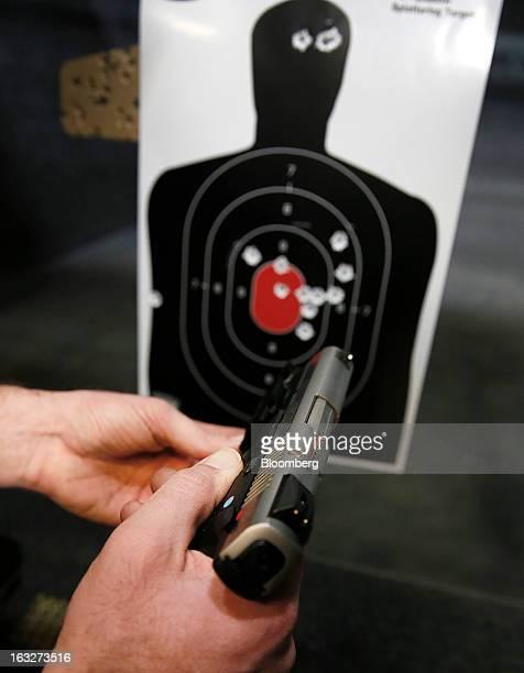 A customer loads a Ruger SR9 9mm handgun at the Rangemasters of Utah gun range in Springville Utah US on Thursday Feb 28 2013 President Barack Obama...
