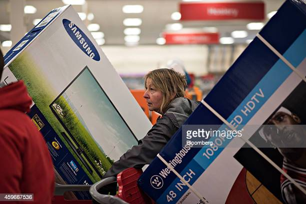 A customer loads a television into a shopping cart at a Target Corp store ahead of Black Friday in Mentor Ohio US on Thursday Nov 27 2014 An...