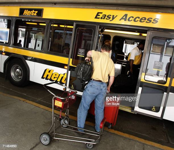 A customer loads his luggage onto a Hertz transport bus outside its rentalcar pickup area July 17 2006 at O'Hare International Airport in Chicago...