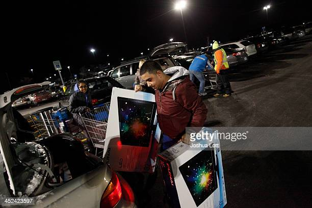 A customer loads televisions into the trunk of a vehicle after shopping at WalMart Thanksgiving day on November 28 2013 in Troy Michigan Black Friday...