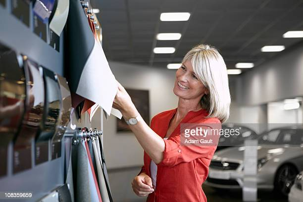 Customer looking at fabric samples in automobile showroom