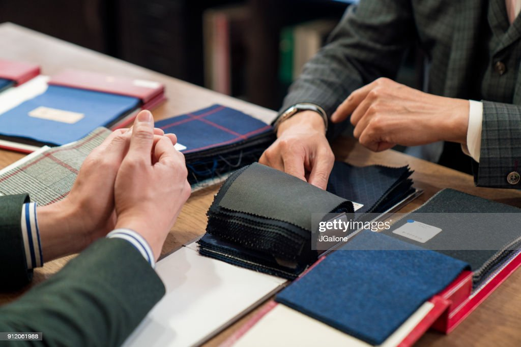 Customer looking at fabric swatches with a tailor : Stock Photo