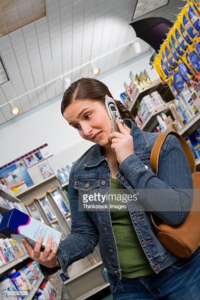Customer looking at medication box and talking on cell phone