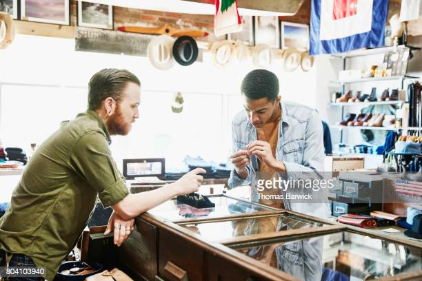 Customer looking at ring while being helped by shop owner in mens boutique