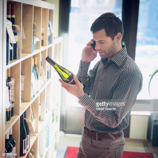 Customer looking at wine bottle and using cell phone in store