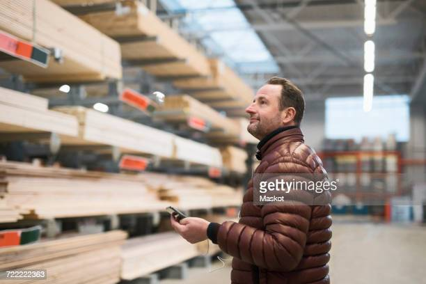 Customer looking at wooden planks on shelves while holding smart phone in hardware store warehouse