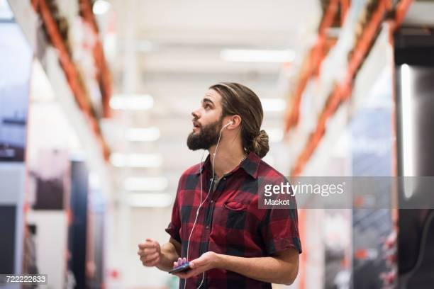 Customer looking up while listening music through smart phone at hardware store