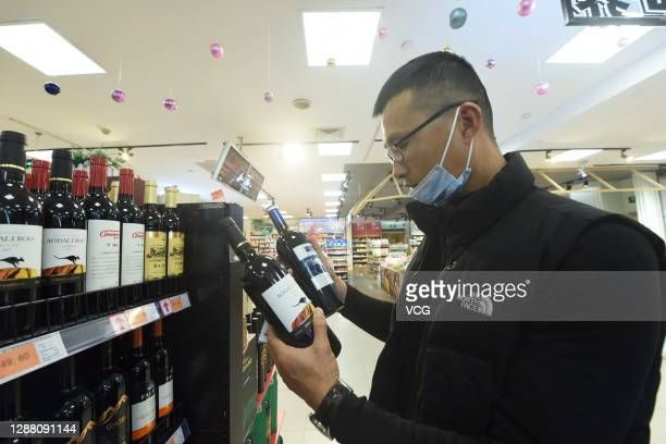 Customer looks at a bottle of wine imported from Australia at a supermarket on November 27, 2020 in Hangzhou, Zhejiang Province of China.