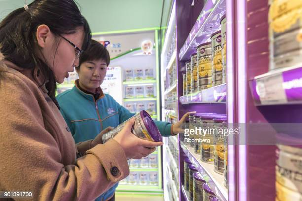 A customer looks at a can of a2 Milk Co Platinum infant formula at a Shanghai Aiyingshi Co Babemax store in Shanghai China on Friday Dec 22 2017...