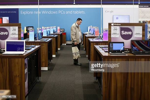 A customer looks at a display of Microsoft Corp Windows computers and tablets inside a Currys PC World electronics store operated by Dixons Retail...