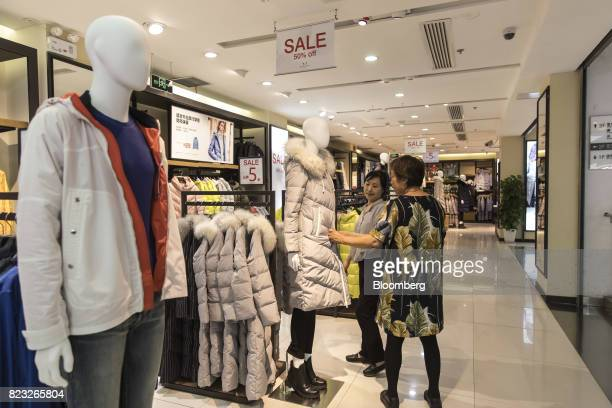 Customer looks at a down jacket displayed inside the Bosideng International Holdings Ltd. Flagship clothing store in Shanghai, China, on Friday, July...