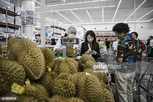 A customer looks at a mobile handset as an employee weighs durian fruit in a WalMart Stores Inc owned and operated Sam's Club store during its...