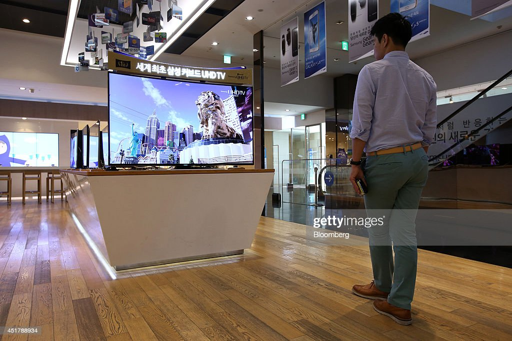 A customer looks at a Samsung Electronics Co. curved Ultra High Definition (UHD) television at the company's d'light store in Seoul, South Korea, on Monday, July 7, 2014. Samsung Electronics is scheduled to report operating profit and sales figures on July 8. Photographer: SeongJoon Cho/Bloomberg via Getty Images