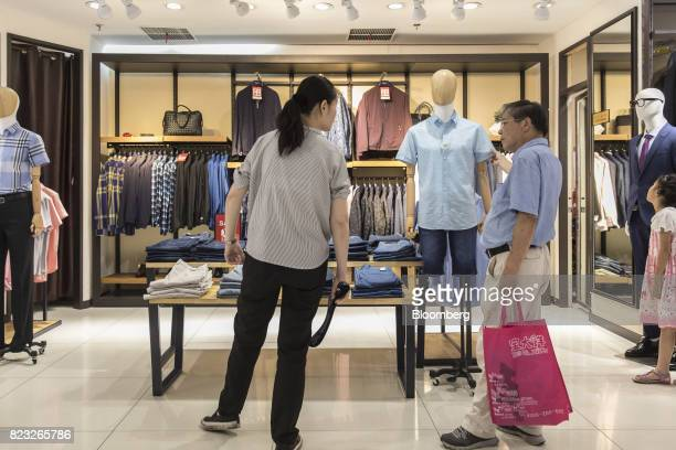 Customer looks at a shirt inside the Bosideng International Holdings Ltd. Flagship clothing store in Shanghai, China, on Friday, July 14, 2017....