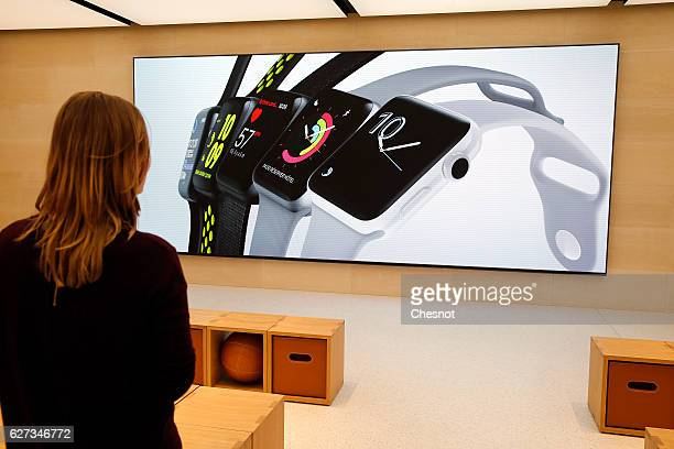 A customer looks at a signage for Apple Watch inside the new Apple store SaintGermain during the first opening day on December 03 2016 in Paris...