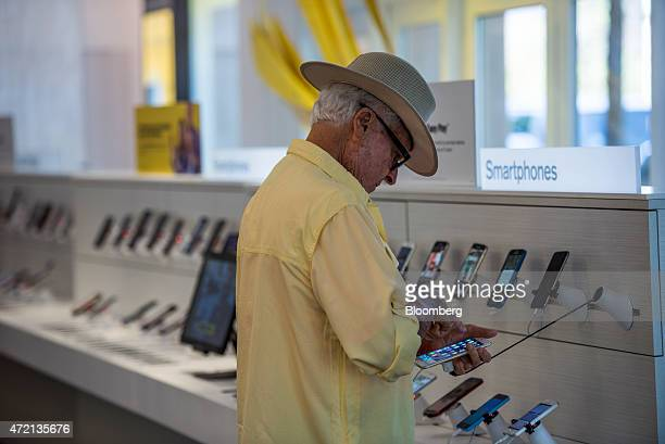 Customer looks at a smartphone at a Sprint Corp. Store in Palo Alto, California, U.S., on Friday, May 1, 2015. Sprint Corp. Is scheduled to release...