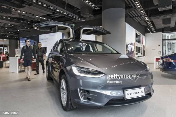 A customer looks at a Tesla Motors Inc Model X electric vehicle on display at the company's showroom in Shanghai China on Tuesday Sept 12 2017 China...