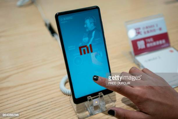 Customer looks at a Xiaomi smartphone in a shop in Beijing on May 3, 2018. - Chinese smartphone maker Xiaomi has kicked off what is expected to be...