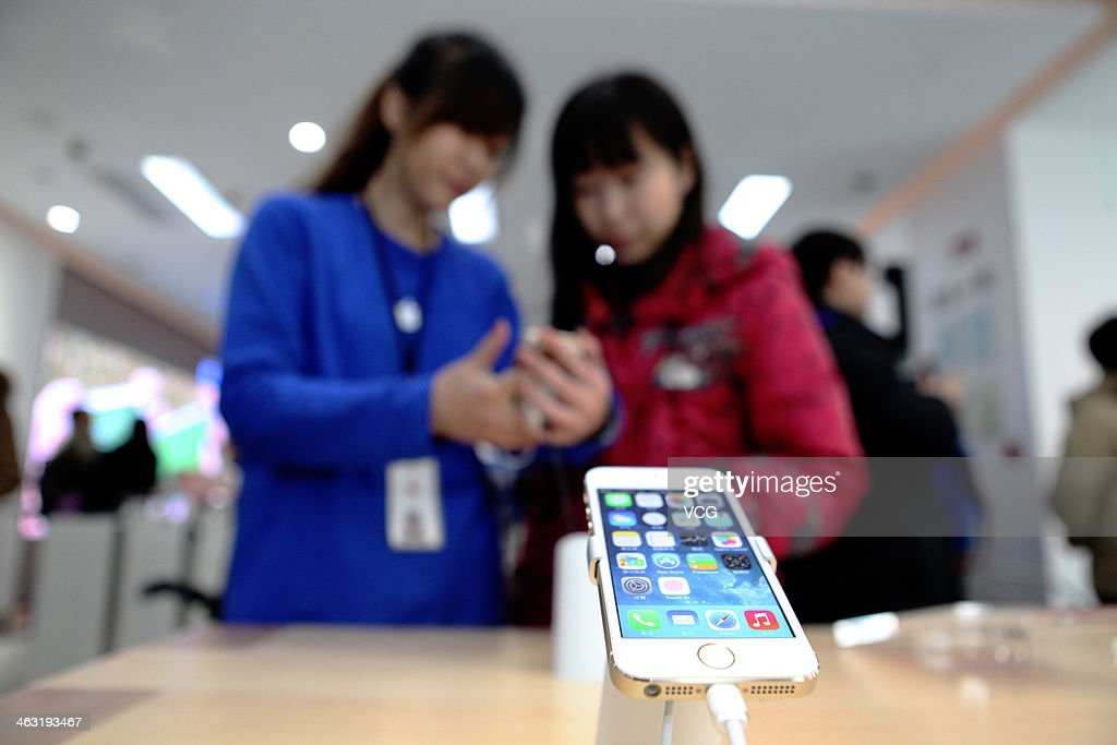 A customer looks at an iPhone 5S on China Mobile's fourth generation (4G) network a China Mobile shop on January 17, 2014 in Beijing, China. Apple Inc. and China Mobile Limited, the world's largest carrier with over 760 million subscribers, signed a deal on December 23, 2013 after six years of negotiations.