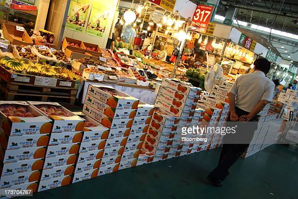 Customer looks at boxes of peaches stacked at Noeun Agricultural and Marine Products Wholesale Market in Daejeon, South Korea, on Tuesday, July 16,...