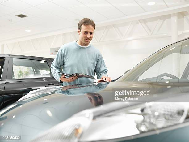 Customer looks at car in car dealership