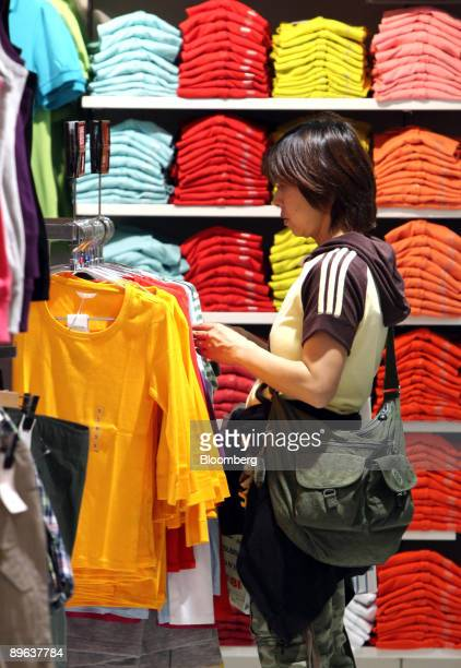 A customer looks at clothes at Fast Retailing Co's Uniqlo shop in the Ginza district of Tokyo Japan on Wednesday July 8 2009 Fast Retailing Co...