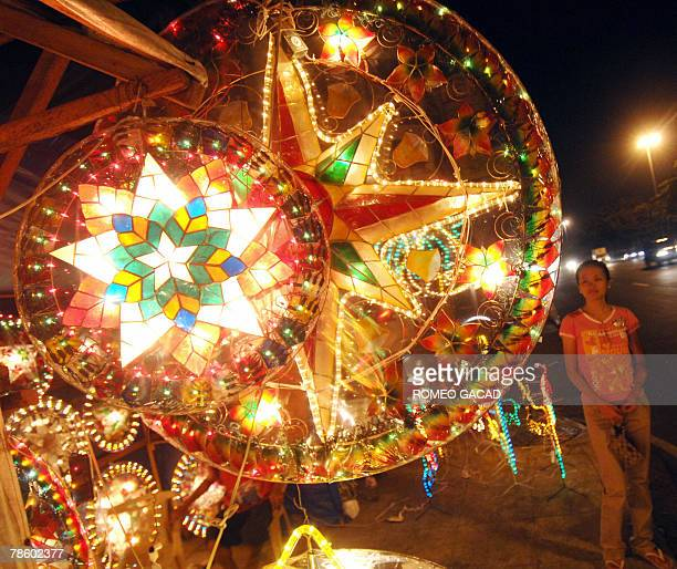 A customer looks at colorful lanterns for sale along a Manila sidewalk 20 December 2007 as Filipino families decorate their house with bright star...