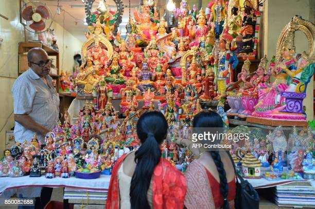 Customer looks at colourful traditional dolls of Gods and characters from the Hindu mythology used as a form of decoration during 'Navarathri'...