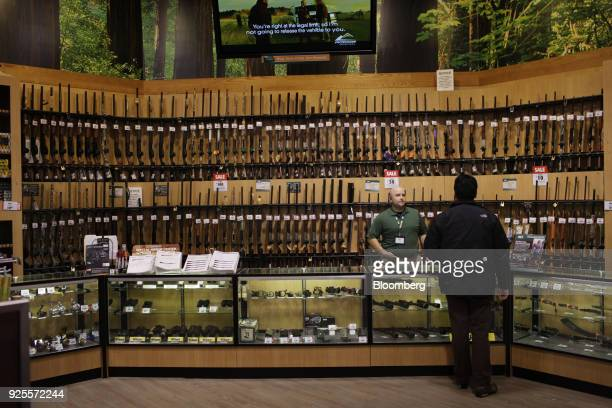 A customer looks at guns at a Dick's Sporting Goods Inc store in Paramus New Jersey US on Tuesday March 6 2012 Dick's Sporting Goods which had 480...