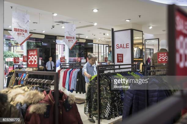 Customer looks at jackets inside the Bosideng International Holdings Ltd. Flagship clothing store in Shanghai, China, on Friday, July 14, 2017....