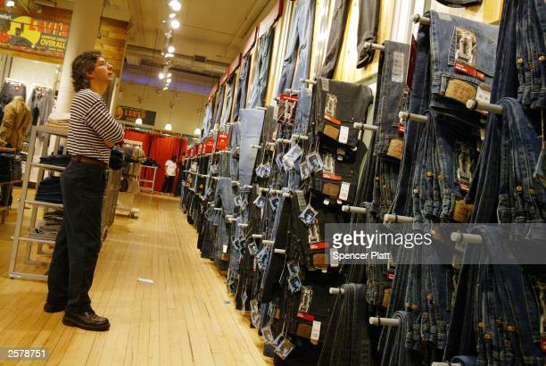 A customer looks at Levi jeans hanging on display at a Levis store October 10 2003 in New York City The jeans maker Levi Strauss Co has revealed an...