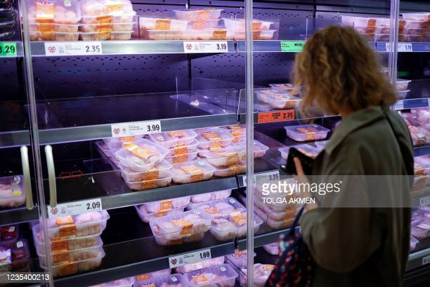 Customer looks at packages of chilled chicken cuts in a half-empty refrigerated display unit at a Lidl supermarket store in Walthamstow, west London,...