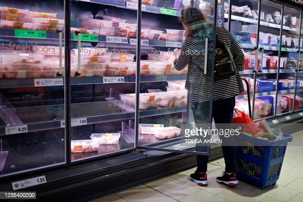 Customer looks at packages of chilled chicken cuts in a part-empty refrigerated display unit at a Lidl supermarket store in Walthamstow, west London,...