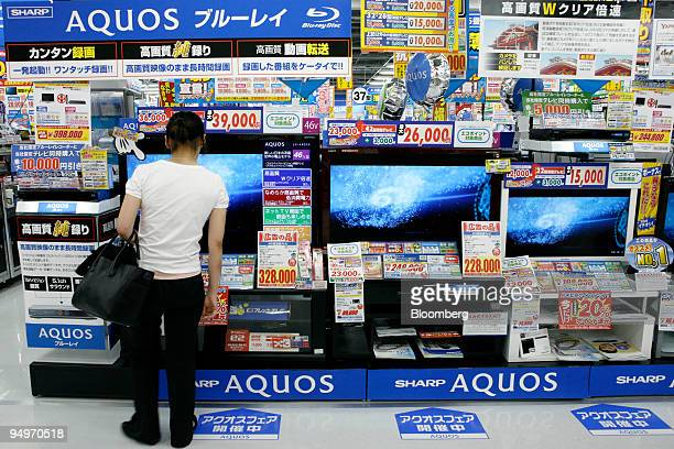 A customer looks at Sharp Corp 'Aquos' liquidcrystal display televisions at an electronics store in Tokyo Japan on Thursday July 30 2009 Sharp Corp...