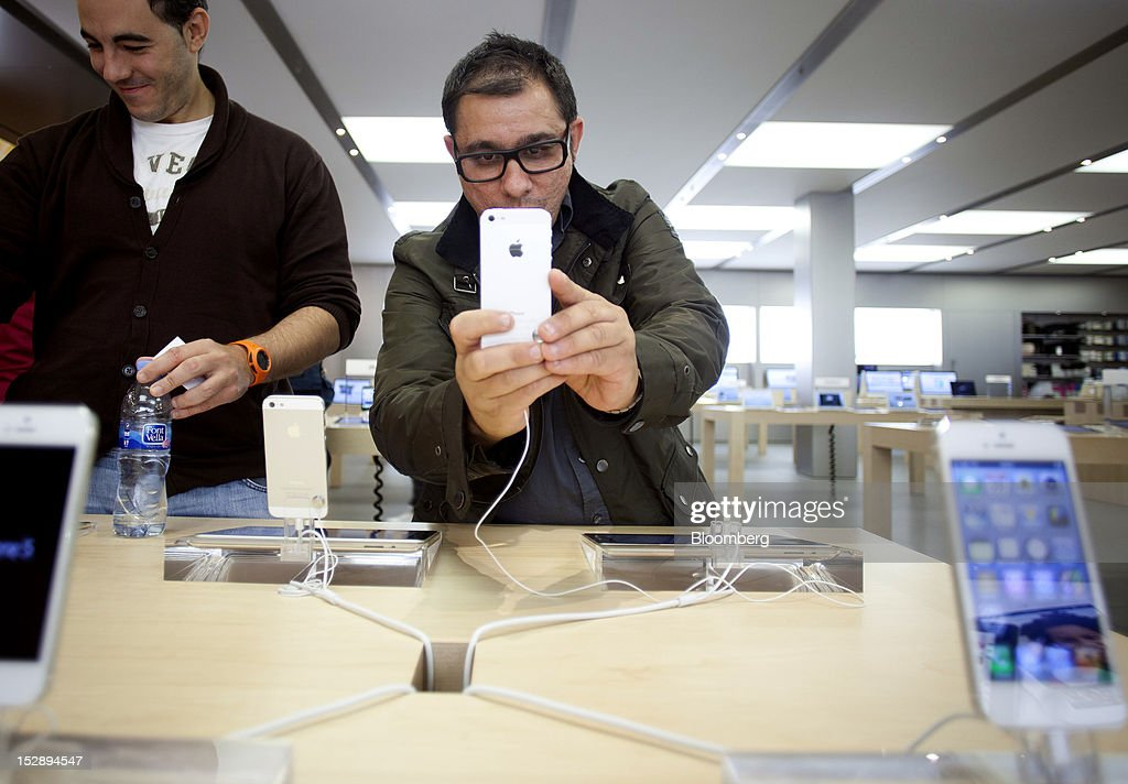 A customer looks at the Apple Inc. iPhone 5 inside the Apple store at the Gran Plaza 2 shopping mall in Majadahonda, near Madrid, Spain, on Friday, Sept. 28, 2012. Apple said it is working to catch up with demand, 'We are working hard to get an iPhone 5 into the hands of every customer who wants one as quickly as possible,' Apple Chief Executive Officer Tim Cook said in a statement. Photographer: Angel Navarrete/Bloomberg via Getty Images