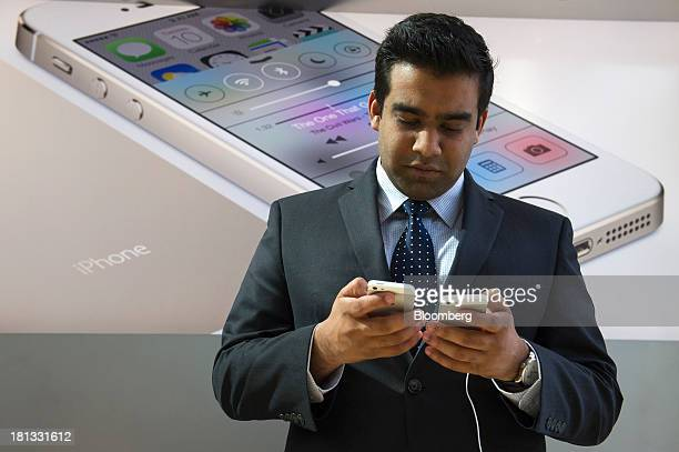 A customer looks at the different Apple Inc iPhone 5s devices during the launch at the company's new store in Palo Alto California US on Friday Sept...