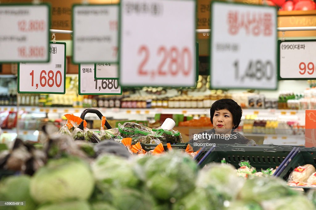 A customer looks at the price of vegetables at an E-Mart Co. store, a subsidiary of Shinsegae Co., in Incheon, South Korea, on Saturday, Dec. 21, 2013. Consumer prices climbed 0.9 percent in November from a year earlier after a 0.7 percent increase in October that was the smallest gain since July 1999. Photographer: SeongJoon Cho/Bloomberg via Getty Images